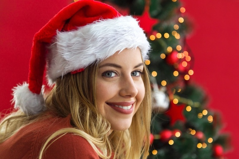 smiling-woman-with-a-santa-hat-free-photo